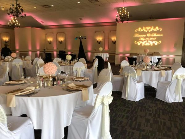 DJ dance floor lighting with pink uplights and custom wedding monogram